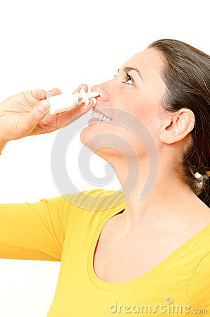 Young woman using nasal spray