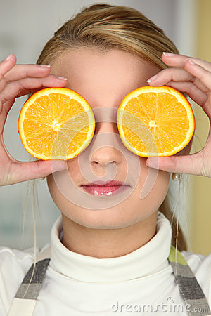 Young woman using orange halves as eyes