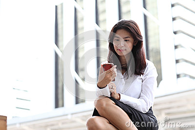 Young woman using a smart phone standing outdoors reading a text