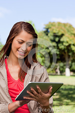 Young woman using a tablet while standing in bright park