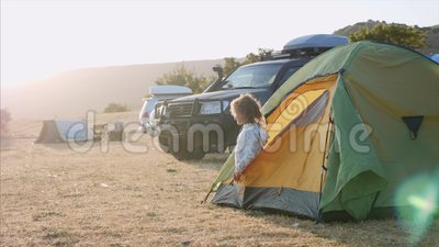 Young woman wakes up and comes out from tourist tent and stretches. At campsite in autumn windy weather. Expedition camp with off-road vehicle on the background stock video