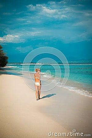 Young woman walking along tropical beach