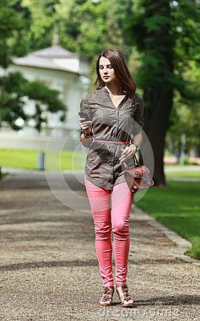 Young Woman Walking in a Park with a Mobile Phone