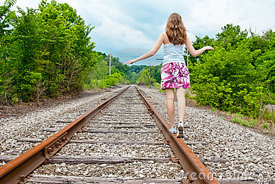 A young woman walking on train tracks