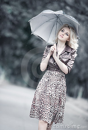 Young woman walking with umbrella