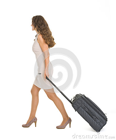 Young woman walking with wheels suitcase