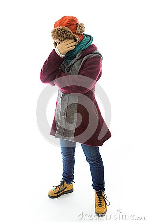 Young woman in warm clothing and covering her face with her hand