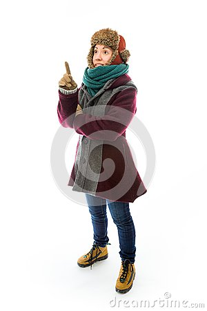 Young woman in warm clothing and pointing upward