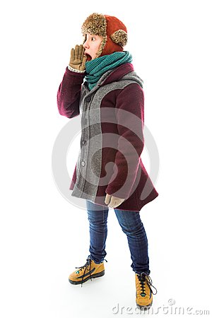 Young woman in warm clothing and shouting with hands cupping mou