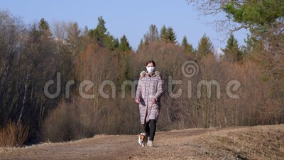 Young woman in warm jacket, wearing virus face mouth mask, walks her dog on country road. Masks are mandatory   outside home. During coronavirus covid-19 stock video footage