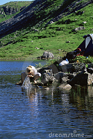 Young woman washing clothes in lake next to tent