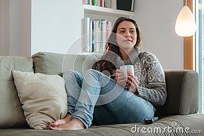 Young woman watching tv home sofa