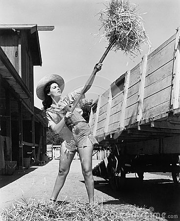 Free Young Woman Wearing Cut Off Jeans And Working At The Farm Pitching Hay Into A Wagon Stock Photos - 52023623