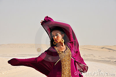 Young woman wearing eastern dress in arabic desert