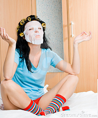 Young woman wearing hair curlers and a mask