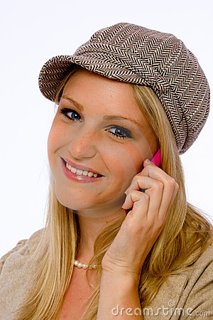 Young woman wearing mod cap smiles at camera