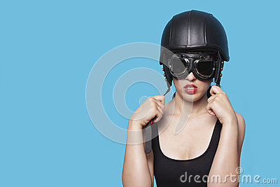 Young woman wearing nostalgic helmet and goggles against blue background
