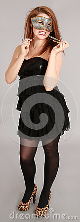Young woman wearing party mask