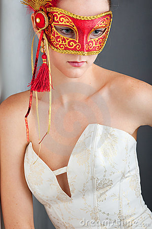 Young woman wearing red carnival mask