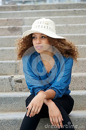 Young woman wearing white hat sitting alone outdoors