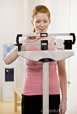 Young woman weighs herself at gym