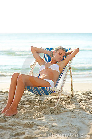Young woman in white bikini on a deck chair
