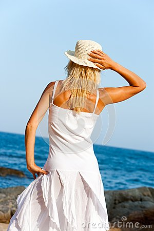 Young woman in white dress on beach.