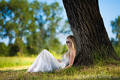 Young woman in white dress relaxing in the park