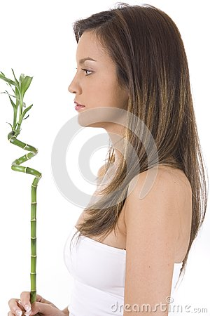 Young woman on white holding green bamboo.