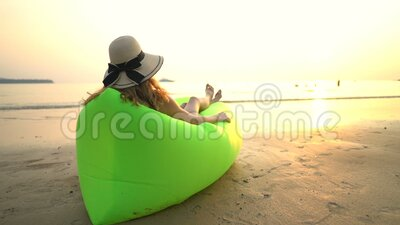 A young woman in a straw hat enjoying peace and privacy at sunset on the beach. A young woman in a wide brimmed straw hat enjoying peace and privacy sitting in stock video