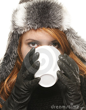 Young woman in winter dress drinking coffee or tea