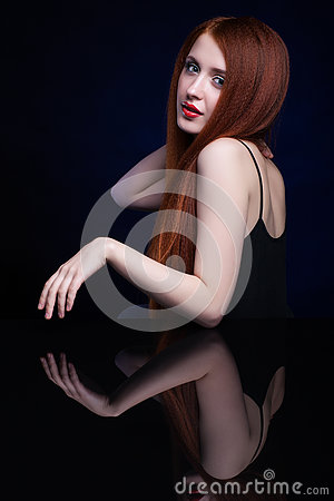Free Young Woman With Ginger Hair Over Reflection Mirror On Blue Back Stock Image - 78197431