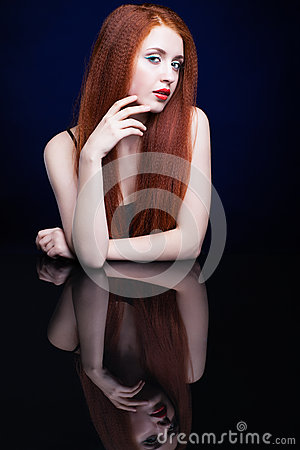 Free Young Woman With Ginger Hair Over Reflection Mirror On Blue Back Stock Photo - 78197440