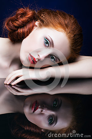 Free Young Woman With Ginger Hair Over Reflection Mirror On Blue Back Royalty Free Stock Photos - 78197538