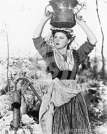 Free Young Woman With Water Bucket On Her Head Next To A Well Stock Photos - 52029263