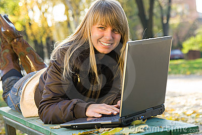 Young woman working with laptop in city park