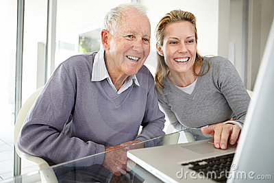Young woman working on laptop with her father