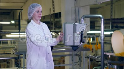 Young woman works with factory equipment in a food production facility. HD stock footage