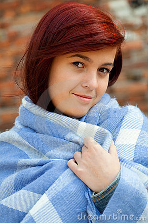 Young woman wrapped in blue blanket, outdoors
