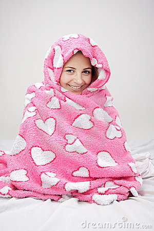 Young woman wrapped in pink blanket