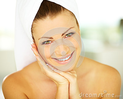 Young woman wrapped in towel with hands on body