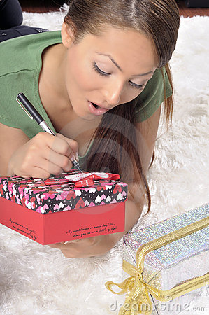 Young woman writing on a gift card on a carpet