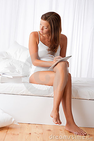 Young woman writing notes and sitting on white bed