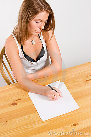 Young woman writing on table