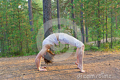 Young woman in Yoga bow pose in the forest