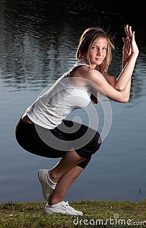Young woman yoga lake