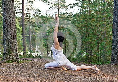 Young woman in Yoga one legged king pigeon pose in the forest