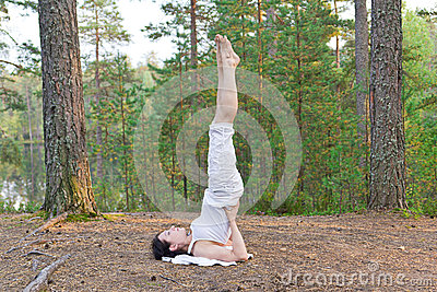 Young woman in Yoga shoulder stand pose in the forest