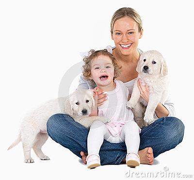 Young woman and young child,Two Labrador puppies