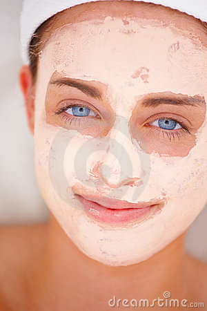 Young womans face covered in facial mask